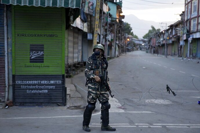 FILE- In this Friday, Aug. 9, 2019 file photo, an Indian Paramilitary soldier patrols during curfew in Srinagar, Indian controlled Kashmir. The main city in the India-administered part of the disputed Himalayan region of Kashmir has turned into a vast maze of razor wire coils and steel barricades as drones and helicopters hover overhead. Wearing flak jackets and riot gear, paramilitary soldiers carry automatic rifles and shotguns to control the network of checkpoints and barricades across roads, lanes and intersections in Srinagar. (AP Photo/ Dar Yasin, File)