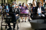 FILE - In this Tuesday, Jan. 12, 2021 photo, Resident Sabeth Ramirez, 80, center, waits in line with others for the Pfizer-BioNTech COVID-19 vaccine at the The Palace assisted living facility in Coral Gables, Fla.  Florida was one of the first states to throw open vaccine eligibility to members of the general public over 65, leading to rumors that tourists and day-trippers are swooping into the state solely for the jab.   Gov. Ron DeSantis said stories of the rich flying to Florida, getting vaccinated and returning home are overblown.  (AP Photo/Lynne Sladky, File)