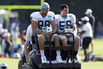Carolina Panthers' Greg Olsen (88) and Luke Kuechly (59) are transported onto the field during an NFL football training camp with the Buffalo Bills in Spartanburg, S.C., Wednesday, Aug. 14, 2019. (AP Photo/Gerry Broome)