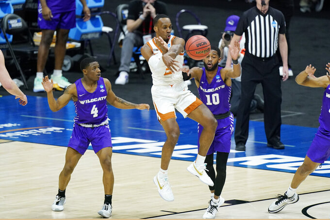 Texas' Matt Coleman III (2) passes the ball away from Abilene Christian's Damien Daniels (4) and Reggie Miller (10) during the first half of a college basketball game in the first round of the NCAA tournament at Lucas Oil Stadium in Indianapolis Saturday, March 20, 2021. (AP Photo/Mark Humphrey)