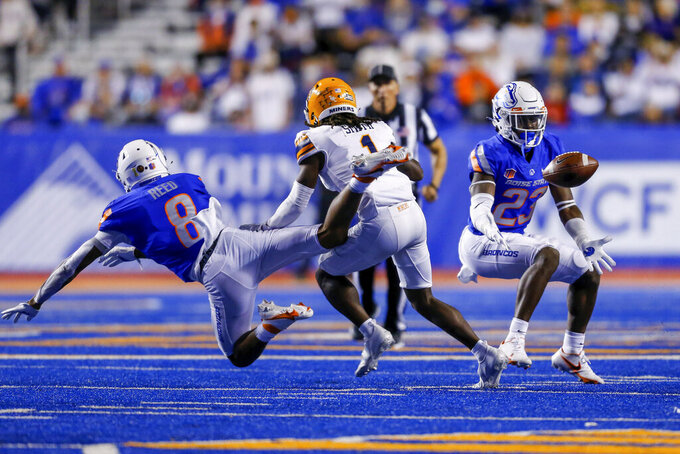 Boise State safety Seyi Oladipo (23) reaches for the ball for an interception after Boise State cornerback Markel Reed (8) tipped the ball away from the hands of UTEP wide receiver Tyrin Smith (1) during the second half of an NCAA college football game Friday, Sept. 10, 2021, in Boise, Idaho. (AP Photo/Steve Conner)