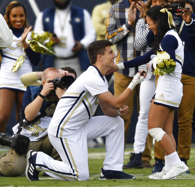 ADDS NAMES: Georgia Tech cheerleader Wilson Harmond, left,  proposes marriage to Dana Francisco during the first half of an NCAA football game between Georgia Tech and Virginia, Saturday, Nov. 17, 2018, in Atlanta. She said yes. (AP Photo/Mike Stewart)