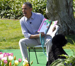 FILE - In this April 1, 2013, file photo, President Barack Obama, accompanied by first dog Bo, reads