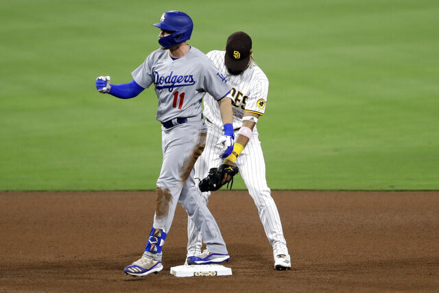 Los Angeles Dodgers' AJ Pollock, left, reacts after hitting an RBI double, next to San Diego Padres shortstop Fernando Tatis Jr. during the seventh inning of a baseball game Tuesday, Aug. 4, 2020, in San Diego. (AP Photo/Gregory Bull)