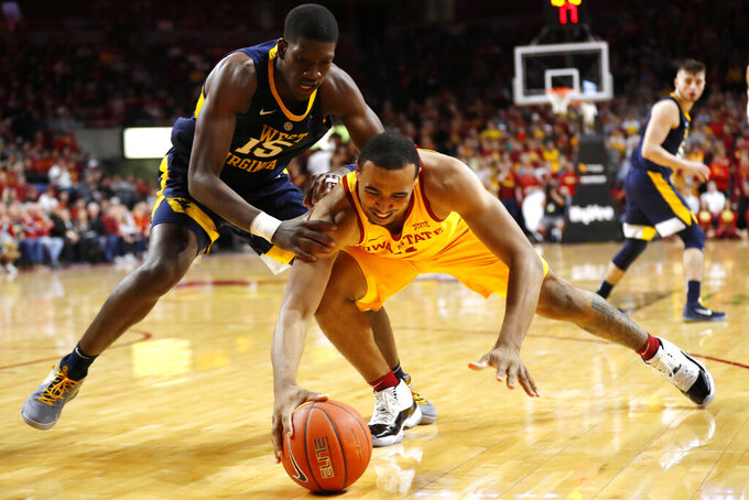 Iowa State guard Talen Horton-Tucker reaches for the ball next to West Virginia forward Lamont West, left, during the second half of an NCAA college basketball game Wednesday, Jan. 30, 2019, in Ames, Iowa. (AP Photo/Charlie Neibergall)
