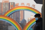 A resident wearing a mask to protect from the coronavirus waits at a bus stop near rainbow decorations on the streets of Beijing on Sunday, Dec. 27, 2020. Beijing has urged residents not to leave the city during the Lunar New Year holiday in February, implementing new restrictions and mass testings after several coronavirus infections last week. (AP Photo/Ng Han Guan)