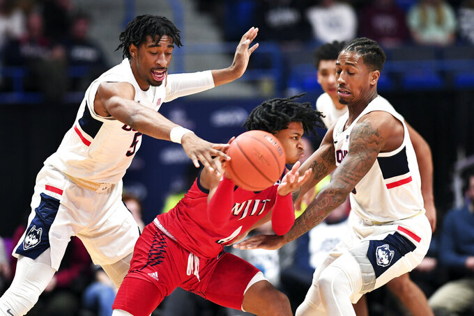 New Jersey Institute of Technology's Zach Cooks (4) is double teamed by Connecticut's Isaiah Whaley (5) and Brendan Adams (10) in the first half of an NCAA college basketball game Sunday, Dec. 29, 2019, in Hartford, Conn. (AP Photo/Stephen Dunn)