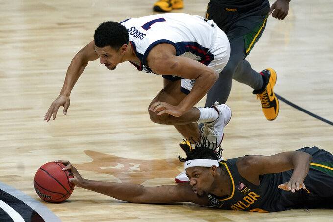 Baylor forward Flo Thamba fights for a loose ball with Gonzaga guard Jalen Suggs (1) during the first half of the championship game in the men's Final Four NCAA college basketball tournament, Monday, April 5, 2021, at Lucas Oil Stadium in Indianapolis. (AP Photo/Michael Conroy)