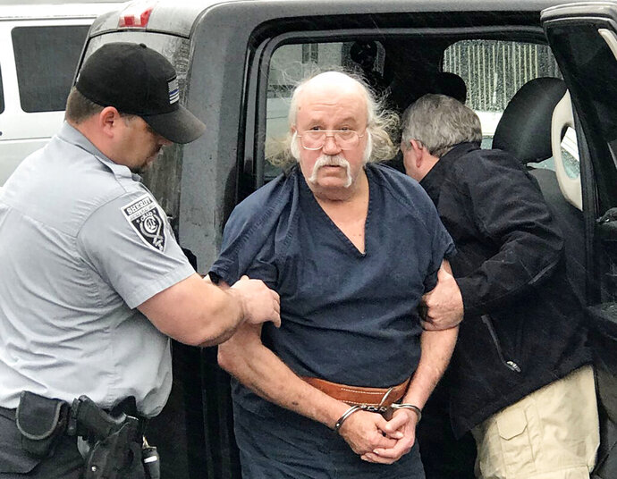 FILE - In this April 25, 2018, file photo, Ronnie Dean Busick arrives at the Craig County Jail in Vinita, Okla. Busick's trial began Friday, Dec. 13, 2019, to determine the mental competency of the Kansas man to stand trial on murder charges in the deaths of a northeast Oklahoma couple and the presumed deaths of their 16-year-old daughter and her 16-year-old friend. (Sheila Stogsdill/Tulsa World via AP, File)