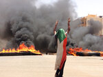 FILE - In this June 3, 2019 file photo, a protester wearing a Sudanese flag flashes the victory sign in front of burning tires and debris, near Khartoum's army headquarters, in Khartoum, Sudan. Sudan's uprising has ushered in a new era both for the nation and for Sudanese women after three decades of autocratic rule by Omar al-Bashir. Sudanese women played a pivotal role in the protests that brought down al-Bashir, and under a joint military-civilian council in power now, they hope for more freedom and equality, and seek to overturn many of the restrictive Islamic laws from the previous era. (AP Photo, File)