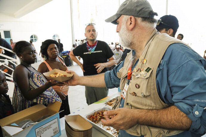 This Sept. 6, 2019 photo released by Amilcar Navarro shows chef Jose Andres distributing food at the Marsh Harbour Government Complex in Abaco, Bahamas, in the wake of Hurricane Dorian. Andres, who has two James Beard Awards and nearly three dozen restaurants, founded the nonprofit World Central Kitchen in 2010 to respond quickly with food and water distribution after natural disasters and other emergencies around the globe. (Amilcar Navarro via AP)