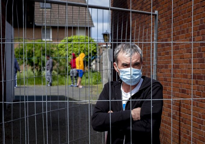 FILE - In this Tuesday, May 12, 2020 file photo, Iulian, Romanian worker who stands behind the fence that was set up at the entrance of a housing of Romania slaughterhouse workers in Rosendahl, Germany. Hundreds of the workers were tested positive on the coronavirus and were put on quarantine.More than 50,000 people have died after contracting COVID-19 in Germany, a number that has risen swiftly over recent weeks as the country has struggled to bring down infection figures. (AP Photo/Michael Probst, file)