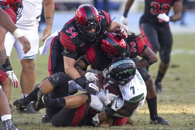 San Diego State defense tackle Hawaii running back Calvin Turner during the second half of an NCAA college football game Saturday, Nov. 14, 2020, in Carson, Calif. (AP Photo/Kyusung Gong)