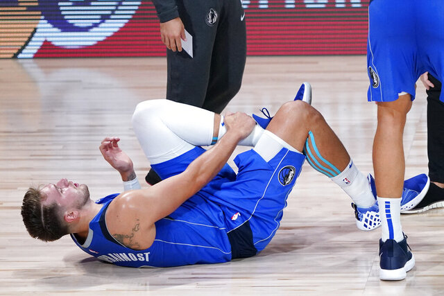 Dallas Mavericks' Luka Doncic (77) grabs his left leg after being injured during the second half of an NBA basketball first round playoff game against the Los Angeles Clippers Friday, Aug. 21, 2020, in Lake Buena Vista, Fla. (AP Photo/Ashley Landis, Pool)