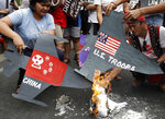 Protesters burn cardboard-cut jet fighters with mock U.S. and China flags as they hold a protest in front of the U.S. embassy in Manila, Philippines on Tuesday, March 5, 2019. The United States is more likely to be involved in a