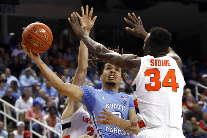 North Carolina guard Cole Anthony drives between Syracuse forward Bourama Sidibe (34) and forward Marek Dolezaj during the first half of an NCAA college basketball game at the Atlantic Coast Conference tournament in Greensboro, N.C., Wednesday, March 11, 2020. (AP Photo/Ben McKeown)