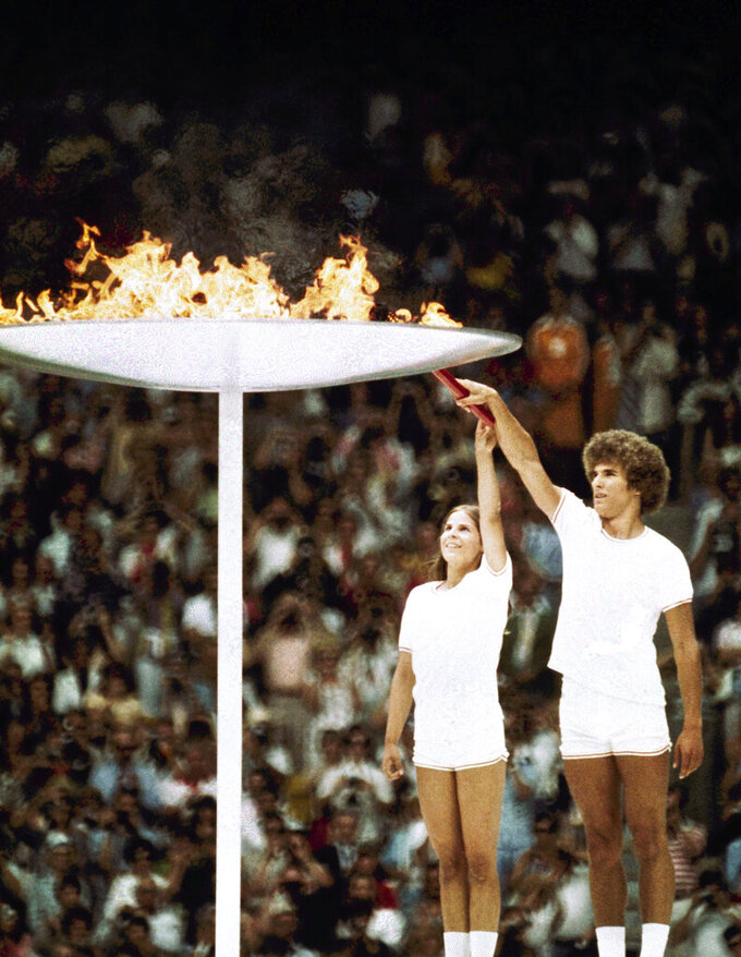Gymnastics athlete Sandra Henderson, left, and track and field athlete Stéphane Préfontaine Lighting of the Olympic Flame during the 1976 Montreal Olympics, July 17, 1976. (AP Photo)