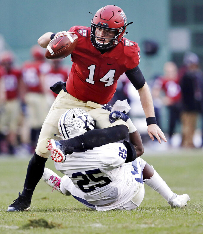 Harvard quarterback Tom Stewart (14) is sacked by Yale linebacker Micah Awodiran (25) during the second half of an NCAA college football game at Fenway Park in Boston, Saturday, Nov. 17, 2018. (AP Photo/Charles Krupa)