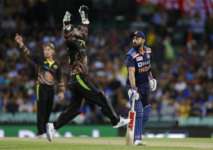 India's captain Virat Kohli, right, watches as Australia's wicketkeeper Matthew Wade, center, jumps to retrieve the ball during the third T20 international cricket match between Australia and India at the Sydney Cricket Ground in Sydney, Australia, Tuesday, Dec. 8, 2020. (AP Photo/Rick Rycroft)