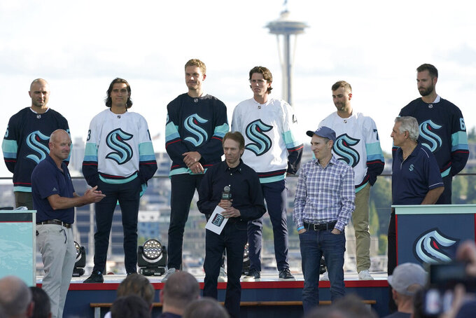 New Seattle Kraken NHL hockey players, back row from left, Mark Giordano, Brandon Tanev, Jamie Oleksiak, Hadyn Fluery, Jordan Eberle and Chris Dreidger stand on stage with Kraken owners David Wright, front left, Jerry Bruckheimer, front center, and Andy Jassy, front second from right, and Kraken general manager Ron Francis, front right, Wednesday, July 21, 2021, after being introduced during the Kraken's expansion draft event in Seattle. Jassy is also president and CEO of Amazon.com. (AP Photo/Ted S. Warren)