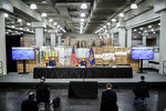 In this March 24, 2020, photo New York Gov. Andrew Cuomo, center, speaks while practicing social distancing against a backdrop of medical supplies during a news conference at the Jacob Javits Center that will house a temporary hospital in response to the COVID-19 outbreak in New York. (AP Photo/John Minchillo)