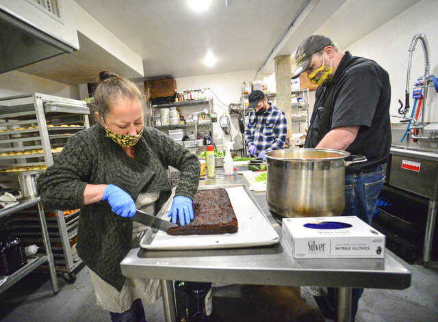 Nicole Reisman, founder of Nicole's Community Kitchen, and helpers, Nathan Shultz and Justin Miglioratti, work on preparing meals at the kitchen of the Stone Church, in Brattleboro, Vt., that are going to be given out on Friday, Dec. 4, 2020. (Kristopher Radder/The Brattleboro Reformer via AP)