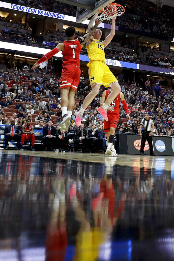 Michigan center Jon Teske, dunks over Texas Tech guard Brandone Francis during the first half an NCAA men's college basketball tournament West Region semifinal Thursday, March 28, 2019, in Anaheim, Calif. (AP Photo/Marcio Jose Sanchez)