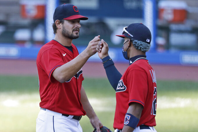 Cleveland Indians relief pitcher Brad Hand, left, is congratulated by Francisco Lindor after the Indians defeated the Chicago White Sox 4-3 in the first baseball game of a doubleheader, Tuesday, July 28, 2020, in Cleveland. (AP Photo/Tony Dejak)