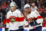 Florida Panthers defenseman Aaron Ekblad (5) skates to the bench while bleeding after being high-sticked, as Josh Brown looks on during the first period of the team's NHL hockey game against the Detroit Red Wings, Saturday, Jan. 18, 2020, in Detroit. (AP Photo/Paul Sancya)