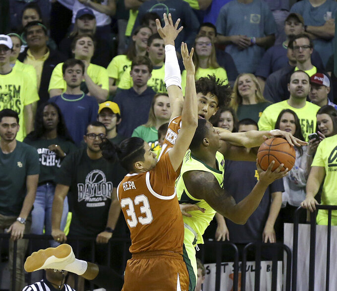 Baylor's Mark Vita has his shot blocked by Texas' Jaxson Hayes as he drives against Texas' Kamaka Hepa during the first half of an NCAA college basketball game Wednesday, Feb. 27, 2019, in Waco, Texas. (Jerry Larson/Waco Tribune-Herald via AP)