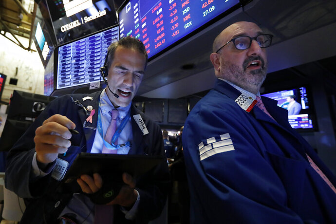 Trader Gregory Rowe, left, and specialist Peter Giacchi work on the floor of the New York Stock Exchange, Thursday, July 18, 2019. U.S. stocks moved lower in early trading on Wall Street Thursday after Netflix reported a slump in new subscribers and dragged down communications companies. (AP Photo/Richard Drew)