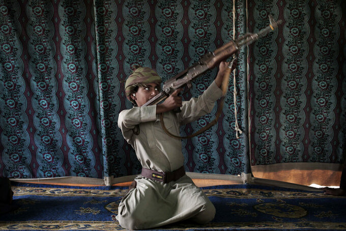 FILE - In this July 27, 2018, file photo, Kahlan, a 12-year-old former child soldier with Yemen's Houthi rebels, demonstrates how to use a weapon at a camp for displaced persons where he took shelter with his family in Marib, Yemen. President Joe Biden's announcement that the U.S. will end its support of a Saudi-led coalition's years-long war against Yemen's Houthi rebels likely will increase pressure on the kingdom to end its campaign there, though reaching an enduring peace for the Arab world's poorest country still remains in question. (AP Photo/Nariman El-Mofty, File)