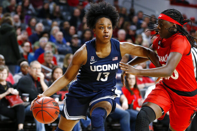 Connecticut guard Christyn Williams (13) drives to the basket against Cincinnati guard Florence Sifa, right, during the first half of an NCAA college basketball game Wednesday, Feb. 26, 2020, in Cincinnati. (AP Photo/Gary Landers)