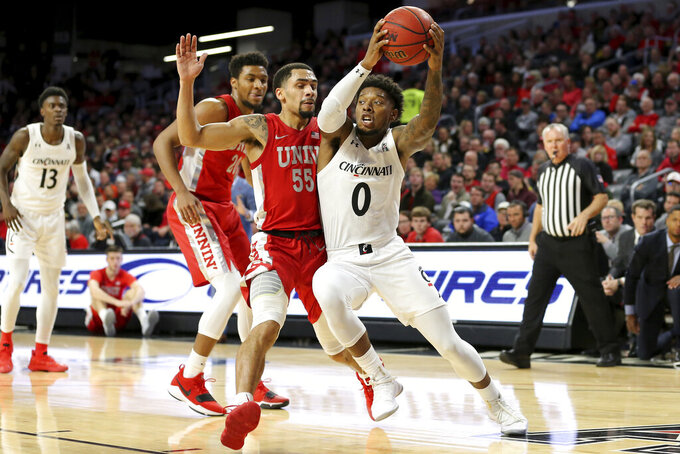 Cincinnati guard Chris McNeal (0) drives to the basket as UNLV guard Elijah Mitrou-Long (55) defends during the first half of an NCAA college basketball game Saturday, Nov. 30, 2019, in Cincinnati. (Kareem Elgazzar/The Cincinnati Enquirer via AP)