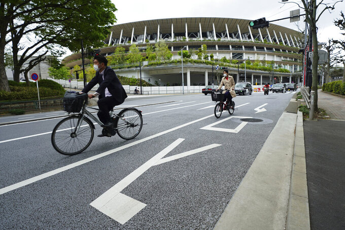 People wearing protective masks to help curb the spread of the coronavirus ride bicycles near the Japan National Stadium, where opening ceremony and many other events are planned for the postponed Tokyo 2020 Olympics, Tuesday, April 6, 2021, in Tokyo. Many preparations are still up in the air as organizers try to figure out how to hold the postponed games in the middle of a pandemic. (AP Photo/Eugene Hoshiko)