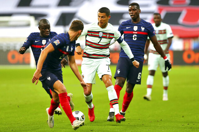FILE - In this Sunday, Oct. 11, 2020 file photo Portugal's Cristiano Ronaldo, center, runs with the ball at France's Benjamin Pavard, foreground, between Ngolo Kante and Paul Pogba, right, during the UEFA Nations League soccer match between France and Portugal at the Stade de France in Saint-Denis, north of Paris, France. The Portuguese soccer federation says Cristiano Ronaldo has tested positive for the coronavirus. The federation says Ronaldo is doing well and has no symptoms. He has been dropped from the country's Nations League match against Sweden on Wednesday, Oct. 14. (AP Photo/Thibault Camus, File)