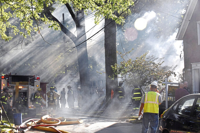 First responders work at the scene of a house fire in Edgewood, Pa,. on Saturday, Sept. 14, 2019. Flames were reported at two homes Saturday afternoon in suburban Edgewood. Emergency officials say one house collapsed and another next door was damaged.  (Christian Snyder/Pittsburgh Post-Gazette via AP)