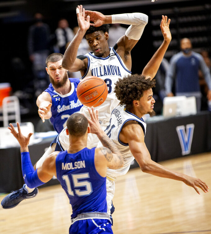 Seton Hall forward Sandro Mamukelashvili, rear, passes the ball to guard Takal Molson (15) under the basket as Villanova forwards Brandon Slater (3) and Jeremiah Robinson-Earl (24) defend during the second half of an NCAA college basketball game Tuesday, Jan. 19, 2021, in Villanova, Pa. (AP Photo/Laurence Kesterson)