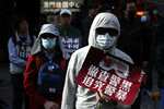 Masked pro-democracy protesters march on a street in Hong Kong, Sunday, Dec. 8, 2019. Marchers are again expected to fill Hong Kong streets Sunday in a rally that will test the enduring appeal of an anti-government movement marking a half year of demonstrations. A placard reads