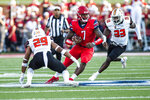 Liberty quarterback Malik Willis (7) carries the ball between Campbell defenders Josh McNeely, left, and Keshawn Thompson during an NCAA college football game in Lynchburg, Va. Saturday, Sept. 4, 2021. (AP Photo/Kendall Warner)