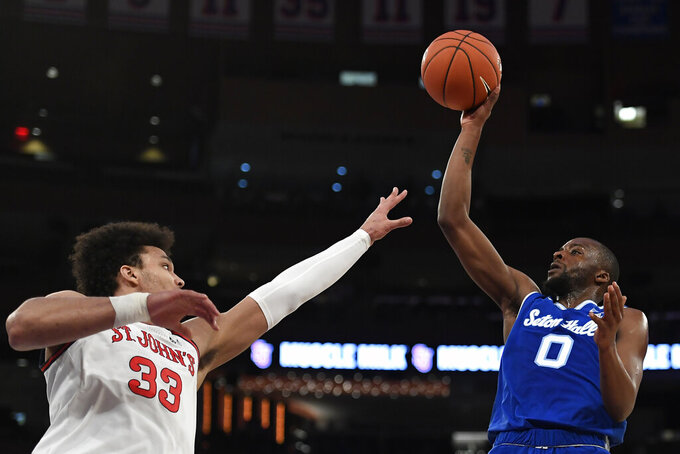 Seton Hall guard Quincy McKnight (0) attempts a basket as St. John's forward Ian Steere (33) defends during the first half of an NCAA college basketball game in New York, Saturday, Jan. 18, 2020. (AP Photo/Sarah Stier)