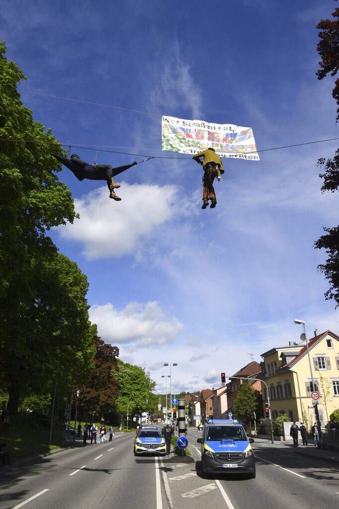 """A climate activist hangs on a rope above the federal highway 32, above him a poster """"Who sows roads, will reap traffic jams"""" in Ravensburg, Germany, Saturday, May 15, 2021. The road has been closed for hours. The police are preparing to clear the road and take the activists down. (Felix Kaestle/dpa via AP)"""