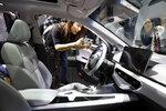 A woman takes a photo of the interior of a new car from Chinese automaker Geely Auto under its new electric brand Geometry during the Auto Shanghai 2019 show in Shanghai Tuesday, April 16, 2019. Automakers are showcasing electric SUVs and sedans with more driving range and luxury features at the Shanghai auto show, trying to appeal to Chinese buyers in their biggest market as Beijing slashes subsidies that have propelled demand. (AP Photo/Ng Han Guan)