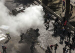 A police armored vehicle sprays tear gar against anti-government demonstrators during a protest in Santiago, Chile, Tuesday, Oct. 22, 2019. Chile has been facing days of unrest, triggered by a relatively minor increase in subway fares. The protests have shaken a nation noted for economic stability over the past decades, which has seen steadily declining poverty despite persistent high rates of inequality. (AP Photo/Esteban Felix)