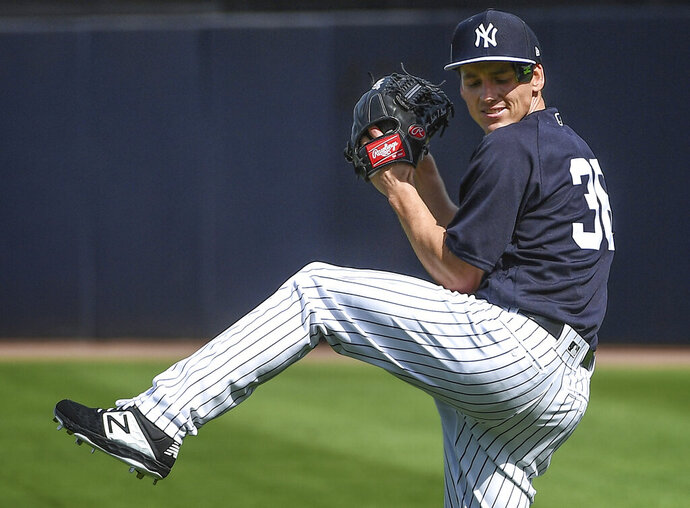 New York Yankees pitcher Danny Farquhar warms up before throwing a bullpen session during baseball spring training Friday, Feb. 15, 2019, in Tampa, Fla. Farquhar is pitching with the Yankees after undergoing brain surgery for a ruptured aneurysm and must wear a special protective cap. (Thomas A. Ferrara/Newsday via AP)