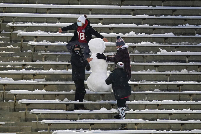 Fans build a snowman in the stands during the second half of an NCAA college football game between Iowa and Wisconsin, Saturday, Dec. 12, 2020, in Iowa City, Iowa. Iowa won 28-7. (AP Photo/Charlie Neibergall)