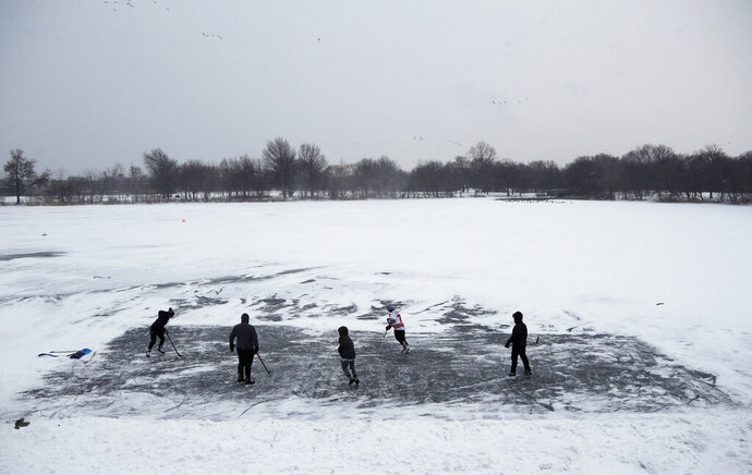FILE - In this Thursday, Jan. 4, 2018 file photo, youths play ice hockey on a frozen pond at Philadelphia's Franklin Delano Roosevelt Park during a winter storm. New concussion guidance shows there isn't enough solid evidence to answer some of parents' most burning questions about contact sports. That includes what age is safest to start playing them. (AP Photo/Matt Slocum, File)
