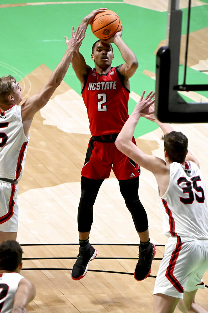 North Carolina State guard Shakeel Moore (2) shoots between Davidson guard Grant Huffman (5) and forward Luka Brajkovic (35) in the first half of an NCAA college basketball game in the first round of the NIT, Thursday, March 18, 2021, in Denton, Texas. (AP Photo/Matt Strasen)