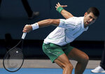 Serbia's Novak Djokovic makes a backhand return to Diego Schwartzman of Argentina during their fourth round singles match at the Australian Open tennis championship in Melbourne, Australia, Sunday, Jan. 26, 2020. (AP Photo/Lee Jin-man)