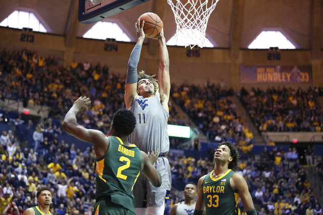 West Virginia forward Emmitt Matthews Jr. (11) shoots while defended by Baylor guard Devonte Bandoo (2) and forward Freddie Gillespie (33) during the second half of an NCAA college basketball game Saturday, March 7, 2020, in Morgantown, W.Va. (AP Photo/Kathleen Batten)